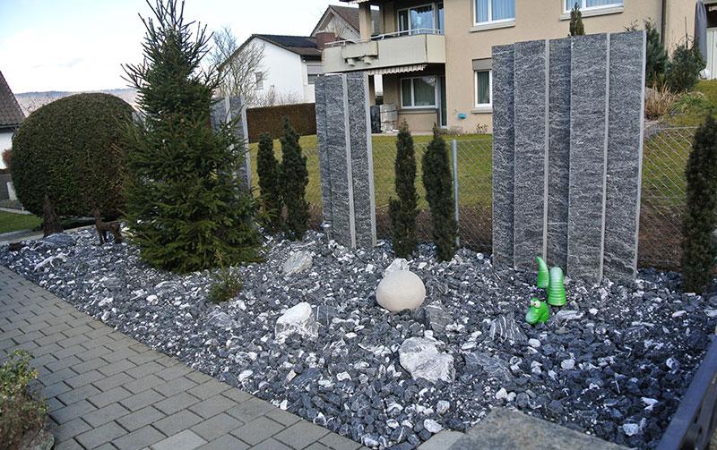 Steingarten aus Alpenkalksteinen und Granitstehlen als Sichtschutz