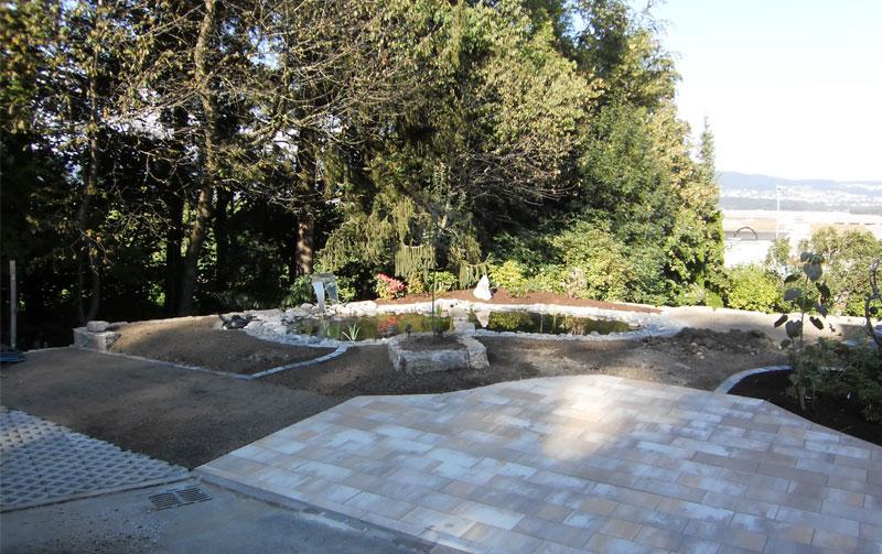 Biotop mit Grünzone und Parkplatz. Parkplatz aus Betonplatten; Farbe: Latte macchiato